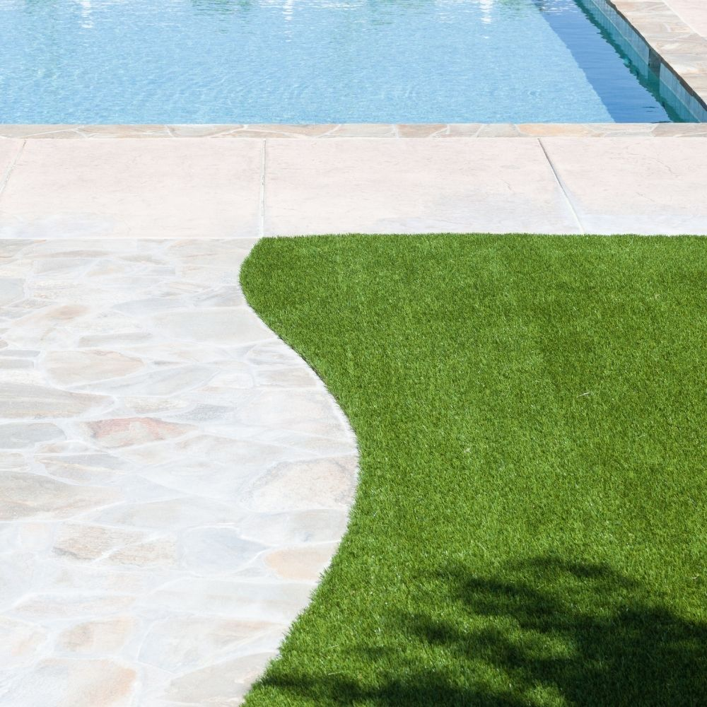 artificial grass installation next to an inground pool with pool deck pavers