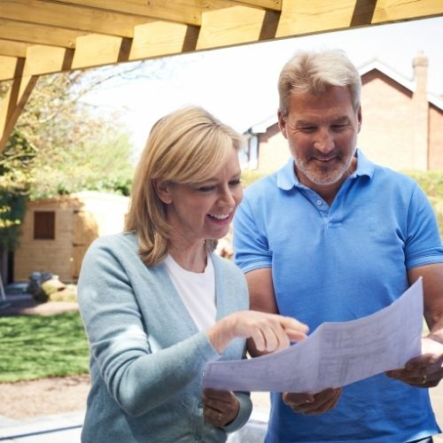 homeowners reviewing the landscape design process in a residential backyard