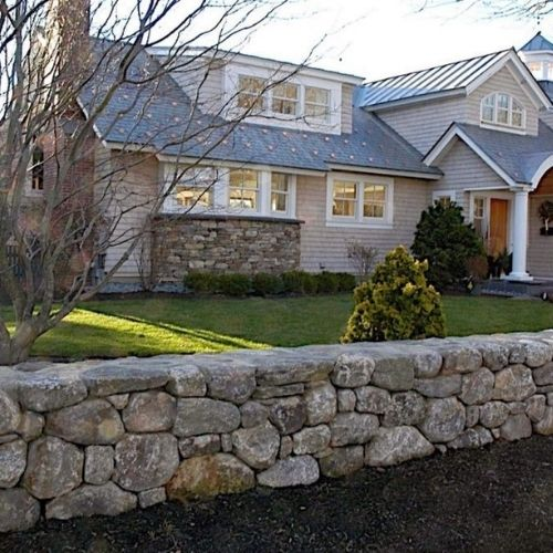 residential new england home with a stone wall and green grass lawn
