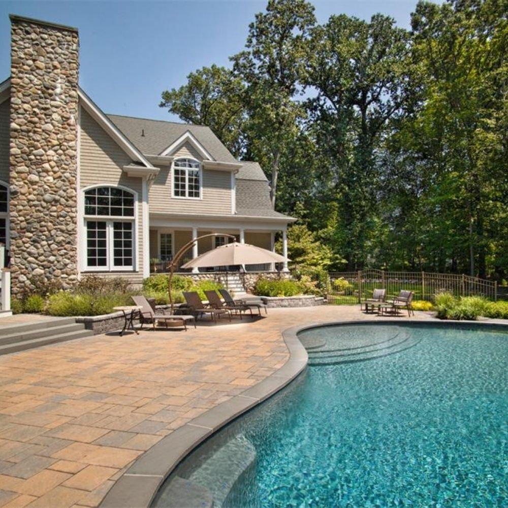 pool deck pavers and an in-ground pool outside of a large New England home on a sunny day