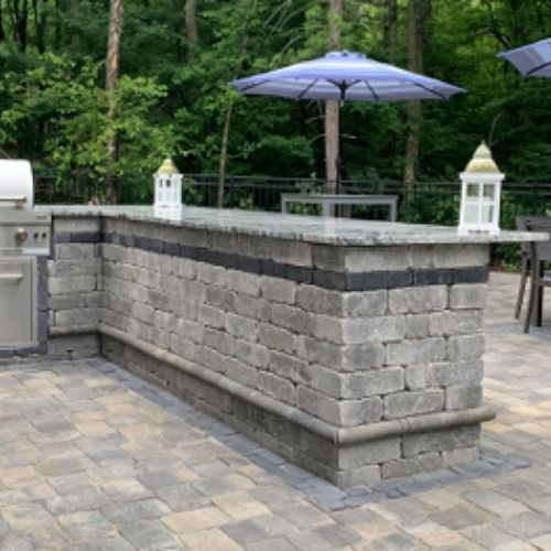 patio pavers and an outdoor kitchen in backyard residence